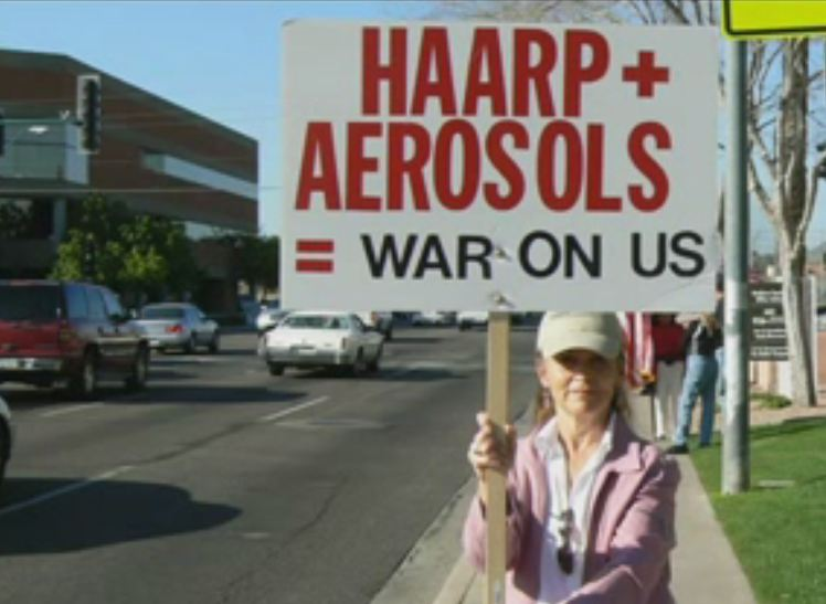 "Protestors holding up signs on street corner that says, ""HAARP and Aerosols = war on us""."