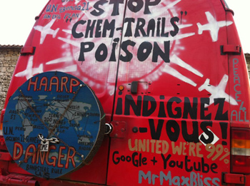 Back of red van that says Stop Cemtrails Poison